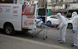 Magen David Adom paramedics in protective gear put a man suspected of having the coronavirus into an ambulance in the the Tel Aviv suburb of Bnei Brak, March 31, 2020. (Gili Yaari/Flash90)