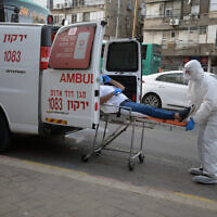 Israeli Magen David Adom medical team members transfer an Israeli man, suspected of being Covid-19 positive, in the Ultra-Orthodox Jewish city of Bnei Brak, March 31, 2020. (Gili Yaari/Flash90)