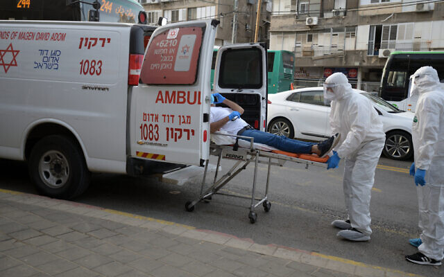 Magen David Adom medical team members transfer an Israeli man, suspected of being Covid-19 positive, in the ultra-Orthodox city of Bnei Brak, March 31, 2020. (Gili Yaari/Flash90)