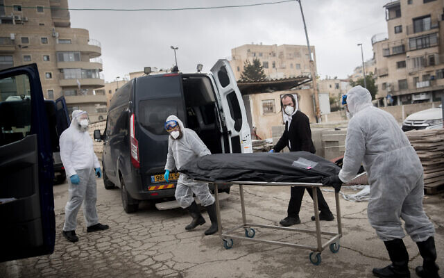 Workers wearing protective clothes carry the body of a patient who died from complications of coronavirus, at the Shamgar Funeral Home in Jerusalem on April 1, 2020 (Yonatan Sindel/Flash90)