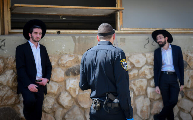 Israeli police officers remove ultra-Orthodox men from the Ponevezh Yeshiva in Bnei Brak, as part of an effort to enforce a lockdown in order to prevent the spread of the coronavirus on April 2, 2020. (Flash90)