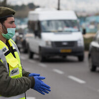 An IDF soldier at a temporary checkpoint in Jerusalem to check that Israelis are not violating restrictions meant to contain the coronavirus, April 2, 2020. (Nati Shohat//Flash90)