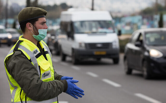 An IDF soldier at a temporary checkpoint in Jerusalem to check Israelis are not violating restrictions meant to contain the coronavirus, April 2, 2020. (Nati Shohat//Flash90)
