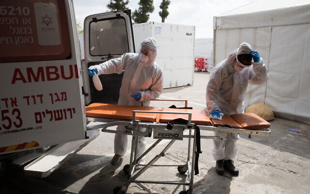 Illustrative: Magen David Adom workers and a Shaare Zedek hospital medical team, wearing protective clothing, as a preventive measure against the coronavirus in Jerusalem on April 2, 2020. (Nati Shohat/Flash90)