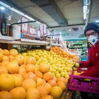 An Israeli shops for groceries at the Rami Levy supermarket in Jerusalem on April 2, 2020. (Yonatan Sindel/Flash90)