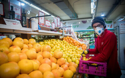 An Israeli shops for groceries at the Rami Levy supermarket in Jerusalem on April 2, 2020. (Yonatan Sindel/Flash90)