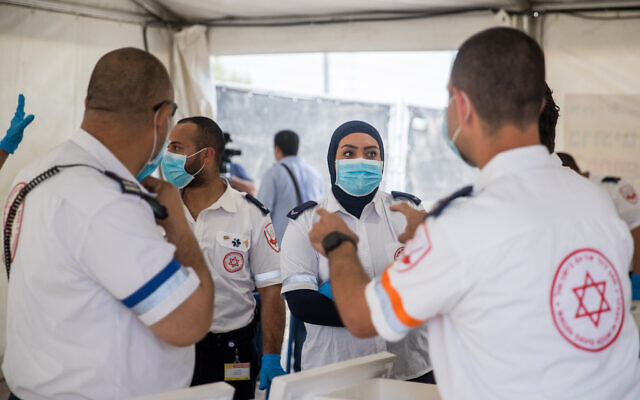 Magen David Adom medical workers seen at a drive-through site to collect samples for coronavirus testing, at the entrance to the East Jerusalem neighborhood of Jabel Mukaber, on April 2, 2020. (Yonatan Sindel/Flash90)