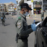 An Israeli border policeman inspects the papers of a driver at a checkpoint located at the exit of the ultra-Orthodox city of Bnei Brak, April 3, 2020. (Gili Yaari /Flash90)