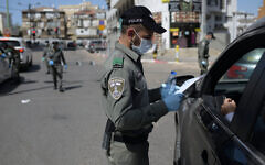 An Israeli border policeman inspects the papers of a driver at a checkpoint located at the exit of the ultra-Orthodox city of Bnei-Brak, April 3, 2020. (Gili Yaari /Flash90)
