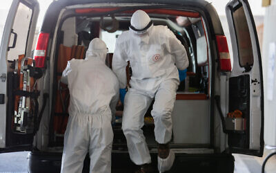 Magen David Adom workers wearing protective clothing, as a preventive measure against the coronavirus evacuate a suspected coronavirus patient to the new coronavirus unit at Shaare Zedek Medical Center, in Jerusalem on April 3, 2020. (Nati Shohat/Flash90)