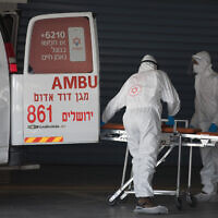 Magen David Adom workers wearing protective clothing evacuate a suspected coronavirus patient outside the new coronavirus unit at Shaare Zedek hospital in Jerusalem, April 3, 2020. (Nati Shohat/ Flash90)