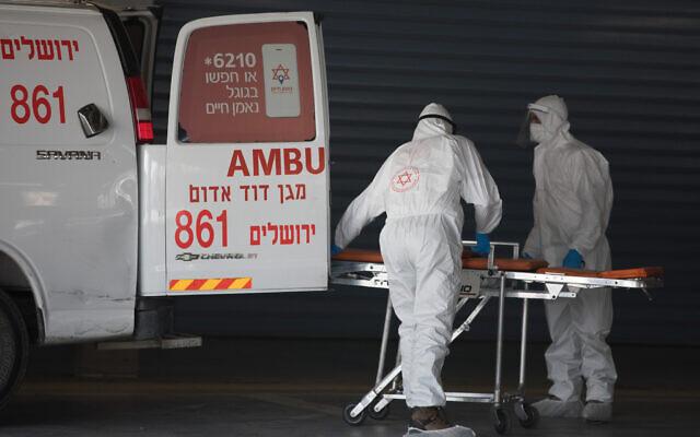 Trabalhadores da Magen David Adom que vestem roupas de proteção evacuam um paciente com suspeita de coronavírus fora da nova unidade de coronavírus no hospital Shaare Zedek, em Jerusalém, em 3 de abril de 2020. (Nati Shohat / Flash90)