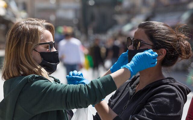Women help each other to put on face masks at the Mahane Yehuda market (Nati Shohat/Flash90)