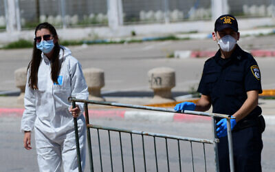 Police and Magen David Adom personnel at a drop off station for residents from the ultra orthodox Jewish city of Bnei Brak who have been infected by the Coronavirus, and on their way to quarantine hotels, near the Ayalon mall on April 3, 2020 (Tomer Neuberg/ Flash90)