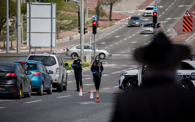 Israeli police officers at a temporary checkpoint in Jerusalem, to check people are not disobeying the governments orders on a partial lockdown, in order to prevent the spread of the Coronavirus on April 3, 2020. (Yonatan Sindel/Flash90)