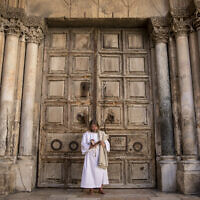A Christian worshiper prays outside the  gates of the Holy Sepulchre Church in Jerusalem, which is closed in line with coronavirus regulations, April 04, 2020. (Olivier Fitoussi/Flash90)