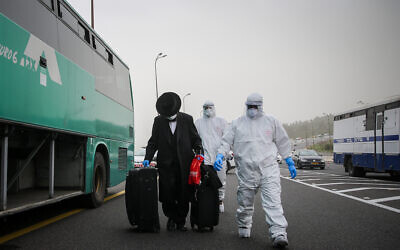 Medics wearing protective clothes walk near a bus with a man who was tested positive for the coronavirus on road number 1 near Jerusalem on April 5, 2020. (Flash90)