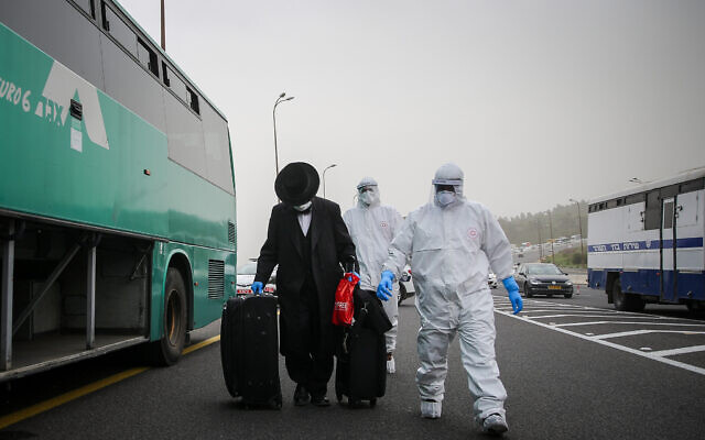 Medics wearing protective clothes walk near a bus with a man who was tested positive for the coronavirus on Route 1 near Jerusalem on April 5, 2020. (Flash90)