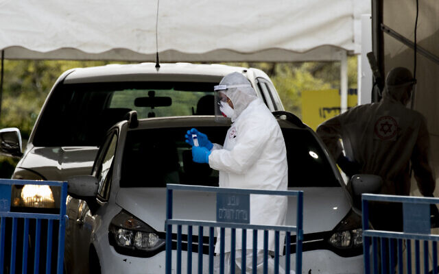 Illustrative: A Magen David Adom paramedic in full protective gear takes samples at a coronavirus 'drive thru' testing in the East Jerusalem neighborhood of Jabel Mukaber on April 5, 2020. (Olivier Fitoussi/Flash90)