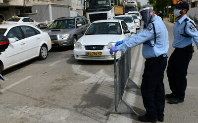 Police officers at a checkpoint located at the entrance to the ultra-Orthodox city of Bnei Brak, April 5, 2020. (Tomer Neuberg/Flash90)