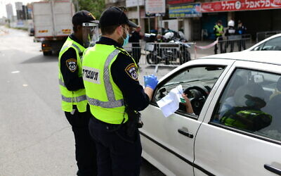 Police officers at a checkpoint located at the entrance to the ultra-Orthodox city of Bnei Brak, April 5, 2020. (Tomer Neuberg/ Flash90)