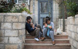 An Israeli family sits on the steps outside their apartment building in Jerusalem, as they stay at home with their children during a nation-wide quarantine, on March 31, 2020. (Hadas Parush/Flash90)
