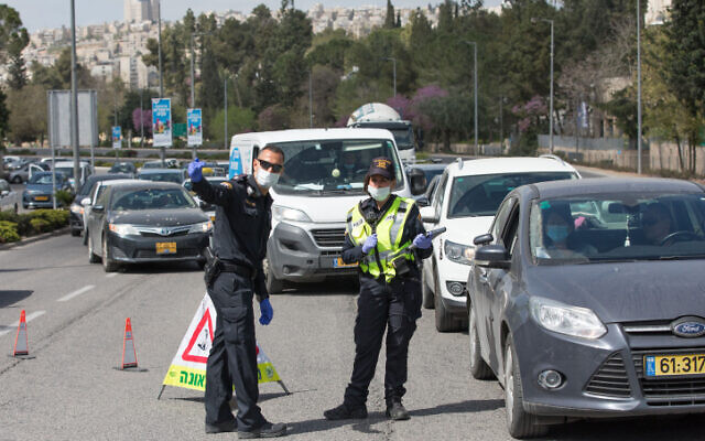 Police at a temporary checkpoint in Jerusalem to check if people are complying with a partial lockdown on April 6, 2020. (Nati Shohat/Flash90)