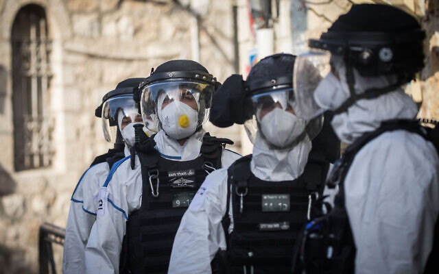 Israel Police officers wearing protective clothing, as a preventive measure against the coronavirus seen after the arrest of a man who tested positive for coronavirus and escaped his quarantine, in the ultra orthodox Jewish neighborhood of Meah Shearim on April 6, 2020. (Yonatan Sindel/Flash90 )