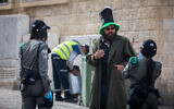 Border Police officers talk to a man in downtown Jerusalem on April 6, 2020. (Yonatan Sindel/Flash90)