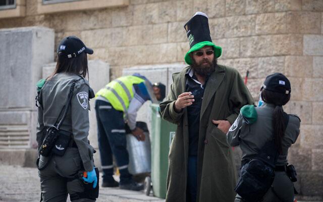 Border Police officers talk to a man in downtown Jerusalem on April 6, 2020. (Yonatan Sindel/Flash90)
