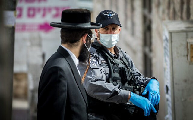 Police officers close synagogues and hand out fines to Haredi Jews in Jerusalem's Bukharim neighborhood, following government restrictions imposed as part of the effort to contain the spread of the coronavirus, April 6, 2020. (Yonatan Sindel/Flash90)