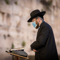 A Haredi man prays at the almost empty Western Wall, Judaism's holiest prayer site, in the Old City of Jerusalem, April 7, 2020. (Nati Shohat/Flash90)