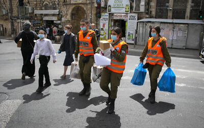 Illustrative: Israeli soldiers of the Home Front Command give out food packages to elderly people obliged to stay home due coronavirus ahead of the Passover holiday, in Jerusalem. April 7, 2020. (Olivier Fitoussi/Flash90)