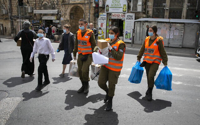 Illustrative: Israeli soldiers of the Home Front Command give out food packages to elderly people obliged to stay home due coronavirus ahead of the Passover holiday, in Jerusalem. April 7, 2020. (Olivier Fitoussi/ Flash90)