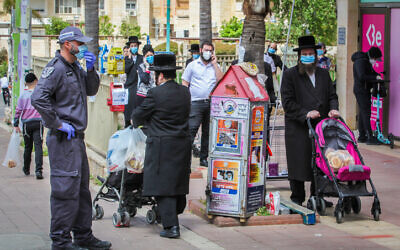 Ultra-Orthodox Jews standing in line outside a supermarket in the central Israeli city of Elad, on April 7, 2020. (Yossi Aloni/Flash90)