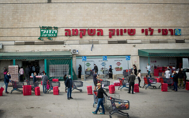 People waiting in line outside Rami Levy supermarket in Jerusalem on April 7, 2020. (Yonatan Sindel/Flash90)