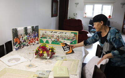 Perahia Shilo arranges the Passover Seder dinner table next to a picture of her children and grandchildren, on the eve of the Jewish holiday of Passover, in the West Bank settlement of Efrat, April 8, 2020. (Gershon Elinson/Flash90)