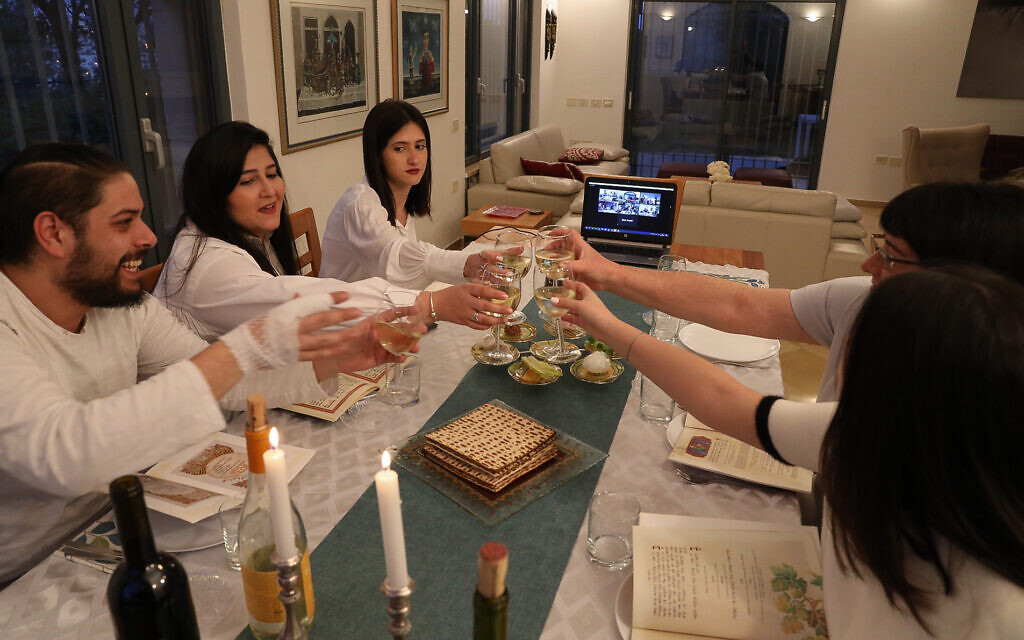 An Israeli family celebrates the Passover Seder with family through a video chatting app on the first night of the Jewish holiday in Tzur Hadassah on April 8, 2020. (Nati Shohat/Flash90)