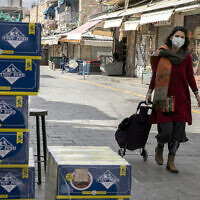 A woman walks past boxes of matza for sale at the Mahane Yehuda market in Jerusalem on April 8, 2020. (Olivier Fitoussi/Flash90)