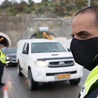 Police at a temporary 'checkpoint' on Highway 60 outside Jerusalem on April 10, 2020, to check if people are disobeying the government's orders on a partial lockdown, in order to prevent the spread of the coronavirus. (Nati Shohat/Flash90)