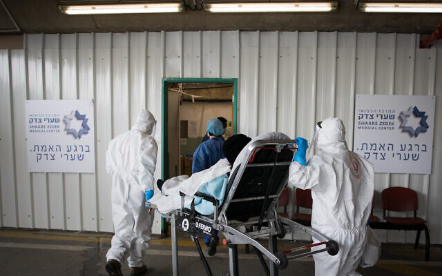 Magen David Adom workers wearing protective clothing with a patient with suspected coronavirus at Shaare Zedek hospital in Jerusalem on April 10, 2020 (Nati Shohat/Flash90)
