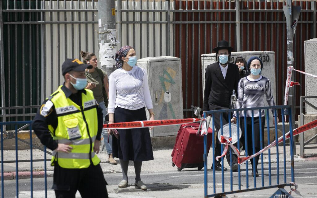 Ultra-Orthodox pedestrians cross an Israeli police roadblock in an ultra-Orthodox neighborhood of Jerusalem  on April 19, 2020.(Olivier Fitoussi/Flash90)