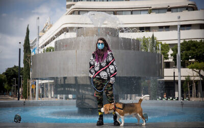 A woman wearing a protective face mask with her dog in Dizengoff Square in Tel Aviv, April 11, 2020. (Miriam Alster/Flash90)