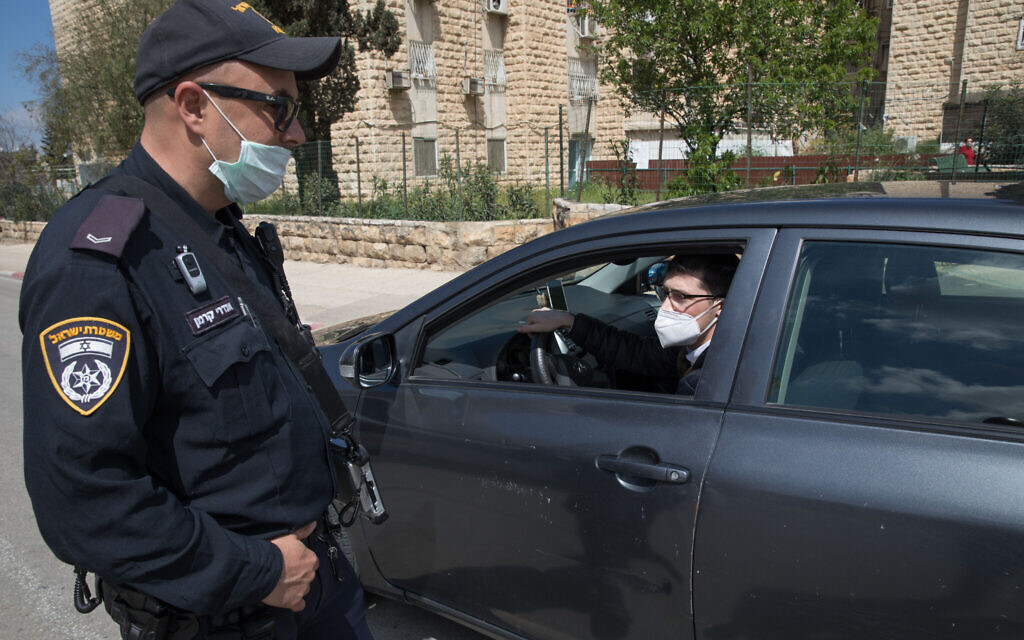 An Israel Police officer at a temporary checkpoint at the entrance to Neve Yaakov, Jerusalem, April 12, 2020, (Nati Shohat/Flash90)