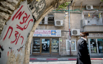 "An ultra-Orthodox man walks past graffiti against Health Minister Yaakov Litzman in Jerusalem's Mea Shearim neighborhood on April 12, 2020. The graffiti reads ""Litzman = murderer."" (Yonatan Sindel/Flash90)"