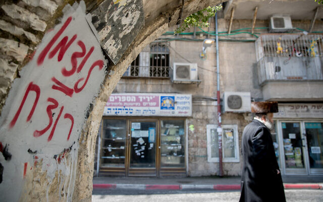 "An ultra-Orthodox man walks past graffiti against Health Minister Yaakov Litzman in Jerusalem's Mea Shearim neighborhood on April 12, 2020. The graffiti reads ""Litzman = murderer."" (Yonatan Sindel/Flash90)"