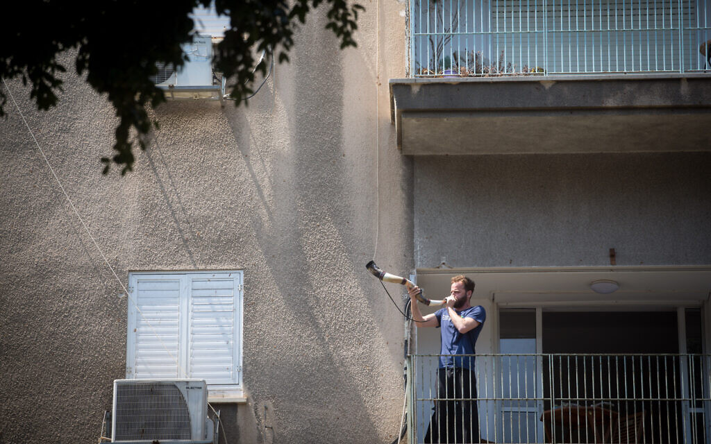 Illustrative: A man blows a shofar horn from his balcony in Tel Aviv on April 14, 2020. (Miriam Alster/Flash90)