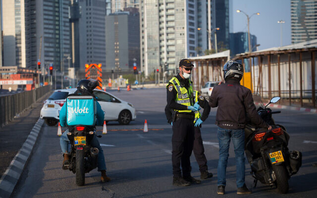 Israeli police officers and Israeli soldiers close Begin road, near the entrance to Ramat Gan in Tel Aviv.  April 14, 2020. All intercity travel has been banned until Thursday morning. (Miriam Alster/Flash90)