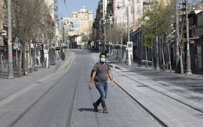 An Israeli man with a face mask walks in an empty street in Jerusalem on April 14, 2020 (Olivier Fitoussi/Flash90