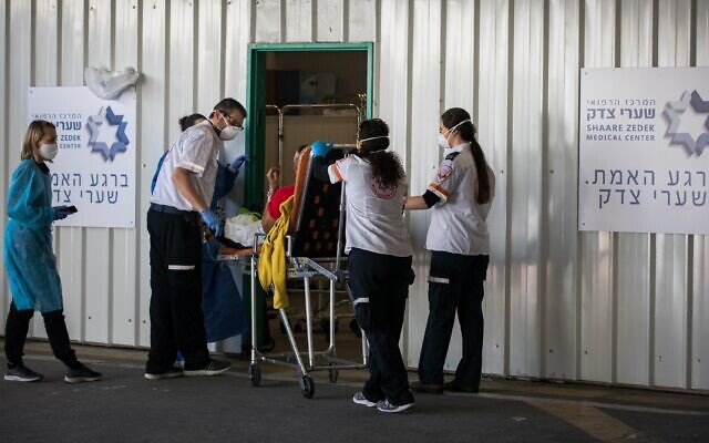Medical personnel at Shaare Zedek Medical Center in Jerusalem receive a patient suspected of having the coronavirus on April 16, 2020. (Nati Shohat/Flash90)